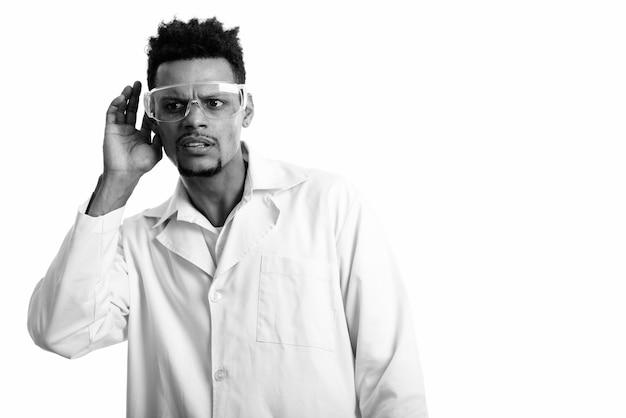 Studio strzałów młodych brodaty lekarz afrykański mężczyzna z okularami ochronnymi na białym tle w czerni i bieli