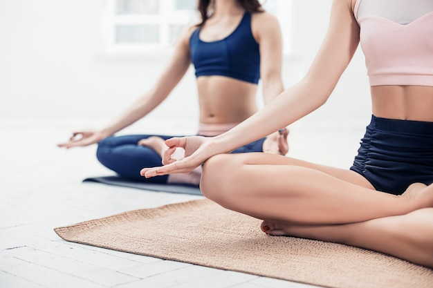 Studio strzałów młodych kobiet ćwiczeń jogi na białym tle
