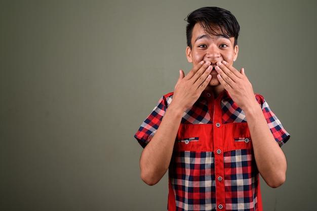 Studio strzałów młodych nastoletnich indianin ma na sobie czerwoną koszulę w kratkę przeciwko kolorowe