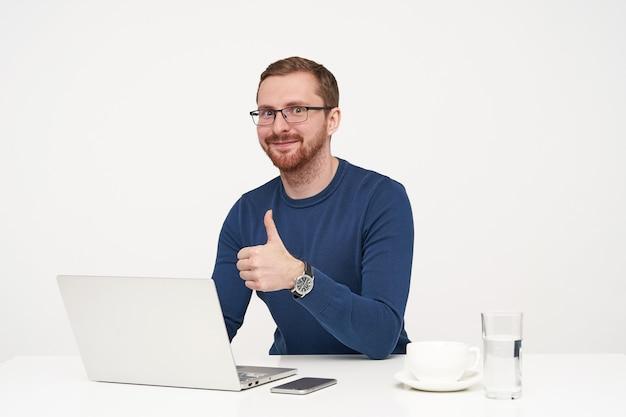 Studio strzałów młodych pozytywnych jasnowłosych mężczyzn w okularach pokazano podniesiony kciuk i lekko uśmiecha się do kamery, siedząc przy stole na białym tle