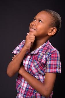 Studio strzałów młodych wieloetnicznego chłopca azji na czarnym tle