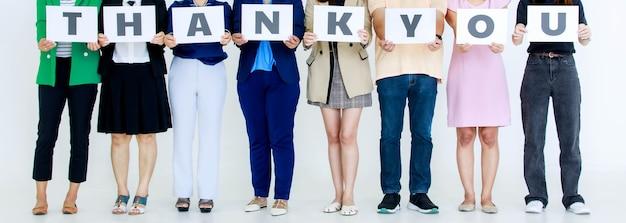 Studio strzałów niezidentyfikowanych niezidentyfikowanych męskich i żeńskich pracowników oficera w biurze firmy trzymać dziękuję alfabet papier kartonowy znak na klatce piersiowej pokazując uznanie dla klienta na białym tle.