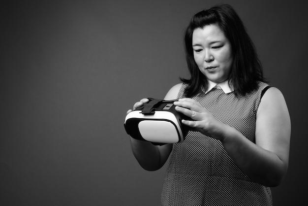 Studio strzałów pięknej nadwagą azji kobieta ubrana w strój na szarym tle w czerni i bieli