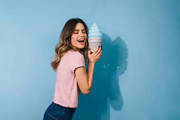 Studio strzałów podekscytowana kobieta z lodami na białym tle na niebieskiej ścianie