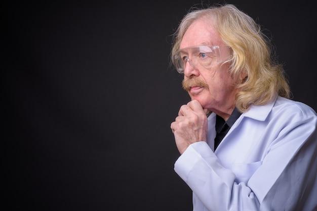Studio strzałów starszy mężczyzna lekarz z wąsem w okularach ochronnych na szarym tle