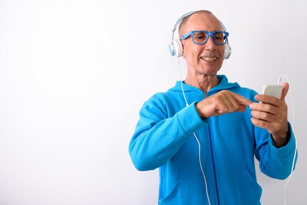 Studio strzałów szczęśliwy łysy starszy mężczyzna uśmiecha się podczas korzystania z telefonu komórkowego