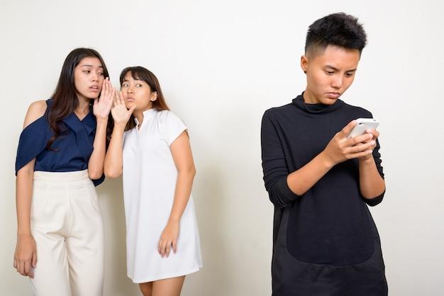 Studio strzałów trzech młodych pięknych azjatyckich kobiet jako przyjaciół razem na białym tle