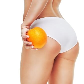 Studio strzałów z atrakcyjną młodą kobietą z pięknym ciałem pomarańczowym na białym tle.