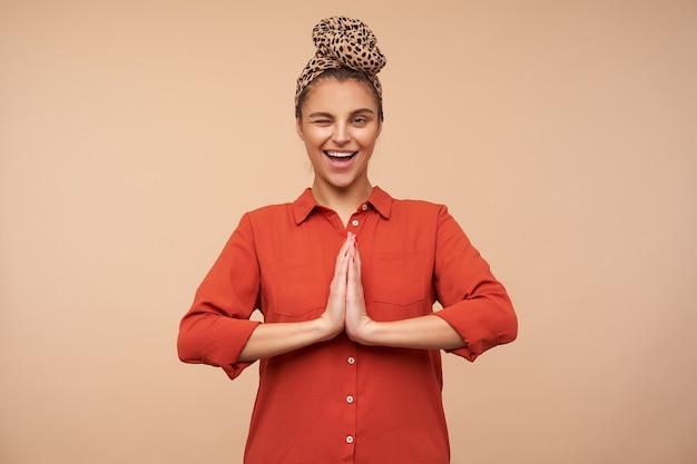 Studio strzałów z radosną młodą uroczą brunetką dając radośnie mrugnięcie z przodu, stojąc na beżowej ścianie z założonymi rękami