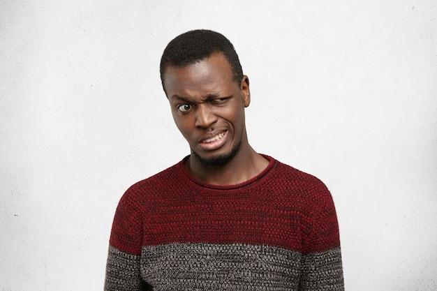 Studio strzałów zdegustowany młody człowiek african american ubrany niedbale