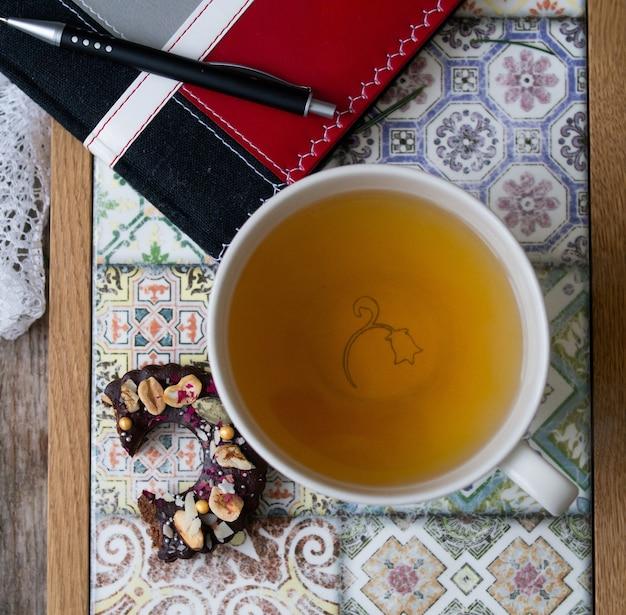 Studio strzelać notatnik, długopis, filiżanka zielonej herbaty, czekoladowe ciasteczka na kolorowej tacy na drewnianym tle. obrabiany przedmiot z notatnikiem i długopisem. planowanie. śniadanie. zbliżenie, widok z góry.
