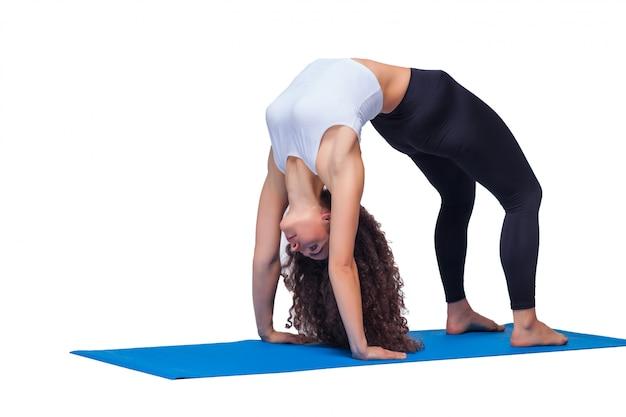 Studio strzelał młoda dysponowana kobieta robi ćwiczeniom joga.