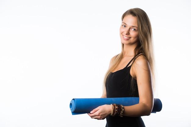 Studio strzelał młoda piękna nastoletniej dziewczyny mienia joga mata i pozować przygotowywam dla gym