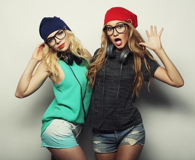 Studio styl życia portret dwóch najlepszych przyjaciółek hipsterskich dziewczyn w stylowych, jasnych strojach, kapeluszach, dżinsowych szortach i okularach, szalejących i świetnie się razem bawiących. młoda i piękna.