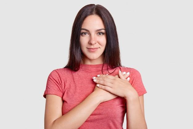 Studio ujęć młodej kobiety o miłym sercu, trzymającej się za ręce na piersi, wyrażającej wdzięczność, ubranej w t-shirt, pozującej na białej, wdzięcznej za pomoc i wsparcie