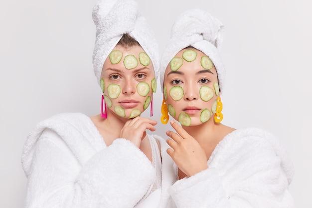 Studio ujęcie dwóch młodych kobiet rasy mieszanej poddawanych zabiegom kosmetycznym w domu, nakładanie plasterków ogórka