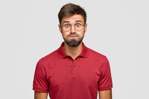 Studio ujęcie emocjonalnego mężczyzny ma niezadowolony wyraz twarzy, dmucha w policzki, wyskoczyły oczy