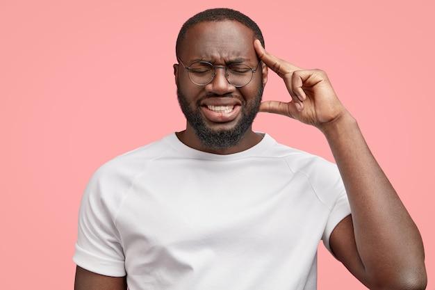 Studio ujęcie przygnębionego ciemnoskórego mężczyzny ma straszny ból głowy, trzyma palce na skroniach, zaciska zęby z bólu