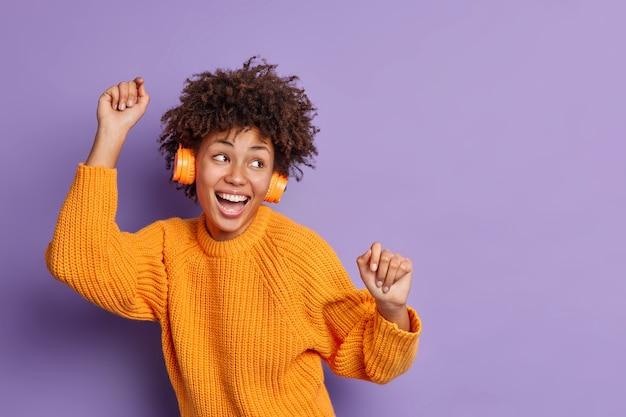 Studio ujęcie uradowanej kobiety porusza się w rytm muzyki, unosi ramiona i czuje się optymistycznie, nosi słuchawki stereo, swobodny sweter