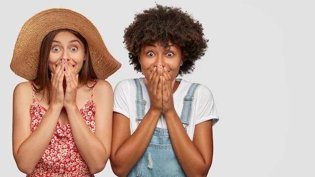 Studio ujęcie zadowolonych, uszczęśliwionych i zaskoczonych kobiet z rasy mieszanej zakrywających usta dłońmi