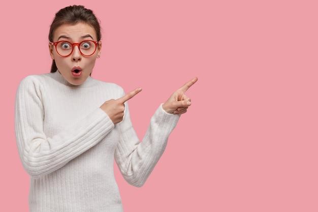 Studio ujęcie zaskoczonej, emocjonalnej kobiety, która jest zdziwiona, wskazuje palcami wskazującymi, wstrzymuje oddech, ubrana w biały sweter