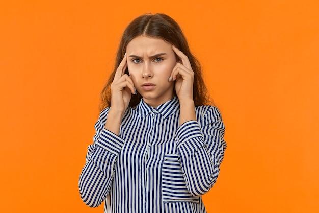 Studio wizerunek stylowej sfrustrowanej i zirytowanej młodej bizneswoman, trzymając palce na skroniach