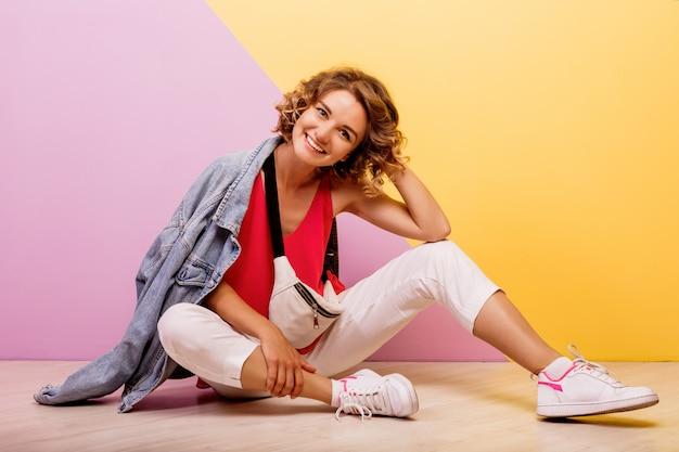 Studio wizerunek uśmiechnięta brunetka piękna kobieta na sobie stylowy sportowy strój i kurtkę dżinsy, siedząc na podłodze.