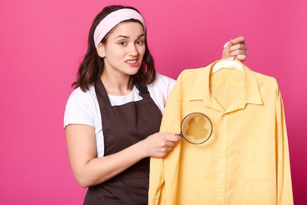 Studio wnętrzowe strzał czarnowłosej emocjonalnej ślicznej młodej kobiety trzymającej szkło powiększające w jednej ręce i jasnożółtą koszulę na wieszaku, plama kawy na ubraniach, niezadowolony z rezultatów prania.