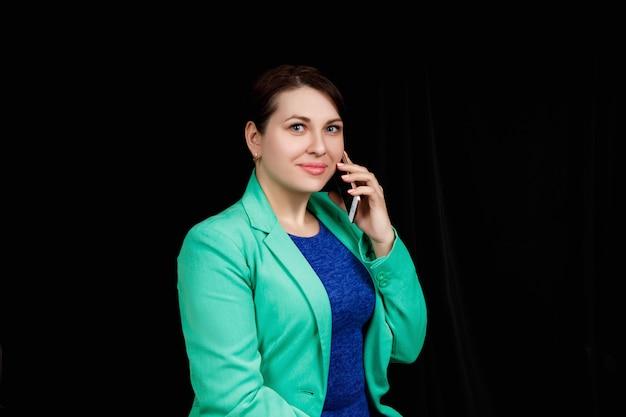 Studio z bliska portret dziewczynki o słowiańskim wyglądzie ubrana w niebieską bluzkę i niebiesko-zieloną kurtkę na czarnej przestrzeni, rozmawiając przez telefon.