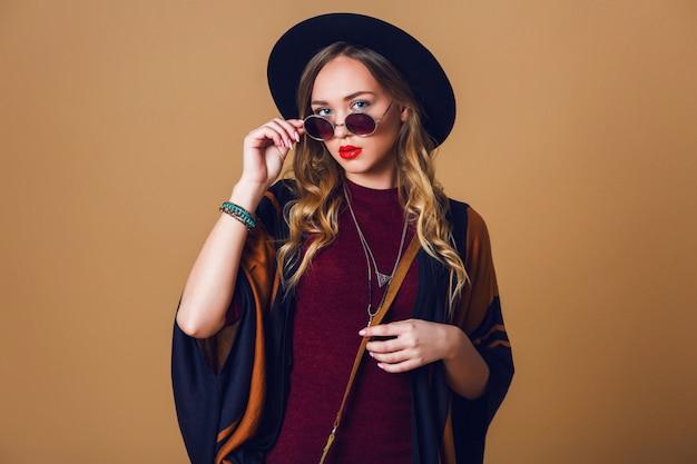 Studio z bliska portret młodej świeżej kobiety blondynka w brązowym słomkowym poncho, wełnianym czarnym modnym kapeluszu i okrągłych okularach patrząc na kamery. torba z zielonej skóry.