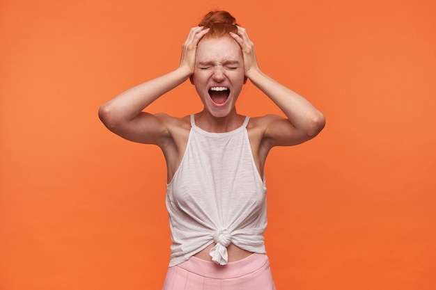 Studio zbliżenie zestresowanej młodej kobiety z lśniącymi włosami uczesanymi w kok stojącej na pomarańczowym tle, trzymającej ręce na skroniach i głośno krzyczącej z zamkniętymi oczami