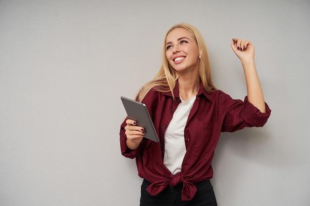 Studio zdjęcie radosnej, uroczej młodej blondynki z rozpuszczonymi włosami, wesoło patrzącej w górę, stojącej na jasnoszarym tle z uniesioną ręką i trzymającej tablet pc