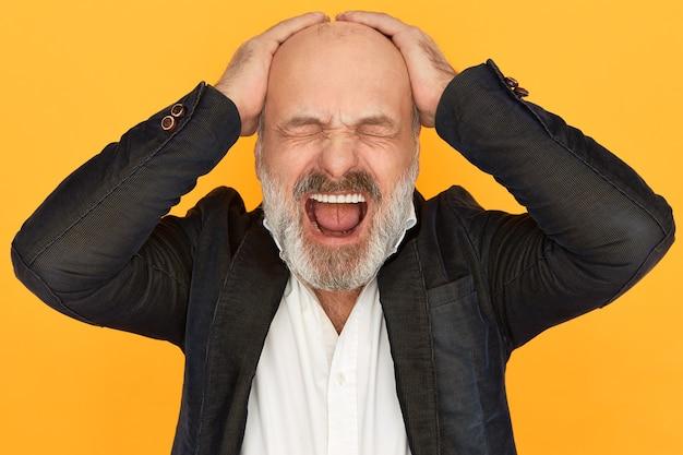 Studio zdjęcie rozwścieczonego, zdruzgotanego starszego biznesmena w oficjalnym ubraniu, zamykającego oczy i głośno krzyczącego, tracącego panowanie nad sobą, trzymającego ręce na łysej głowie, zestresowanego niepowodzeniem biznesowym
