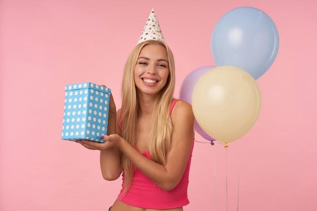 Studio zdjęcie szczęśliwej młodej długowłosej blondynki z przypadkową fryzurą raduje się z miłej imprezy razem z przyjaciółmi, obchodzi urodziny, pozuje na różowym tle z wielokolorowymi balonami powietrznymi