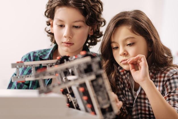 Studiowanie przedmiotów ścisłych. pozytywnie przemyślane i skoncentrowane dzieci siedzące w klasie naukowej i używające gadżetu, wyrażając zainteresowanie