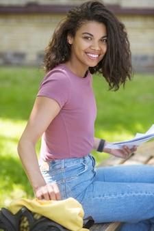 Studiowanie w parku. słodka dziewczyna w różowej koszulce siedząca na trawie w parku