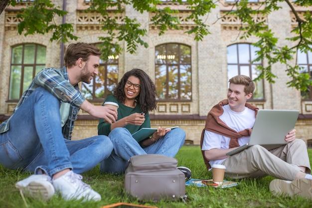 Studiowanie w parku. studenci studiujący w parku i wyglądający na zaangażowanych