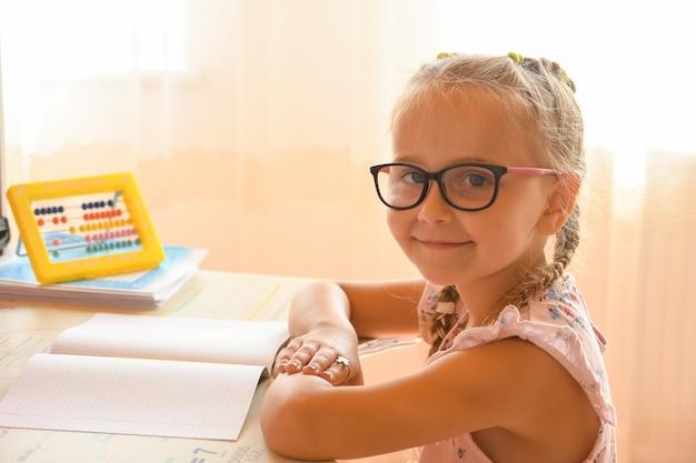 Studiując w domu, portret młodej dziewczyny siedzącej przy biurku w okularach.