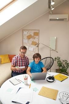 Studiuję pionowe ujęcie online młodego inteligentnego ojca noszącego okulary, który pomaga swojemu synkowi