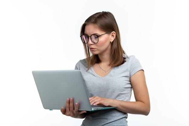 Studium, edukacja, koncepcja ludzi. młoda inteligentna kobieta w okularach wysyłanie sms-ów coś na laptopie.