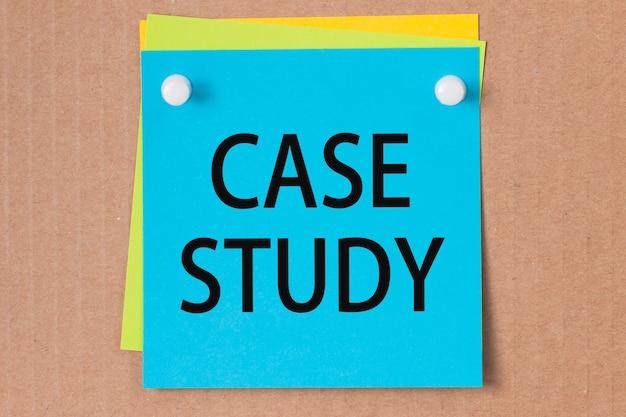 Studium przypadku napisane na niebieskim papierze i przypięte na tablicy korkowej