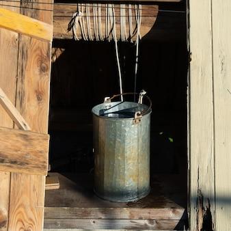 Studnia z otwartymi drzwiami i metalowym wiadrem z wodą