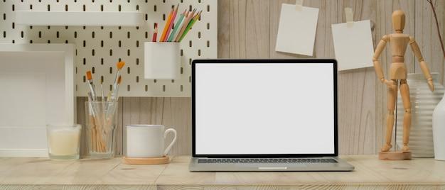 Study story z makietą laptopa, filiżanki, papeterii, narzędzi do malowania i dekoracji na drewnianym stole