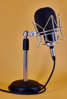 Studyjny mikrofon pojemnościowy do komunikacji rozgłoszeniowej, na stole stoi na pomarańczowym tle