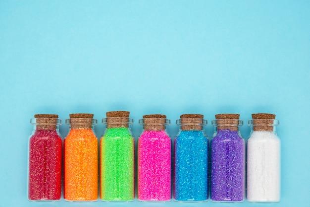 Stwórz koncepcję małych słoików z kolorowymi konfetti na niebieskiej ścianie
