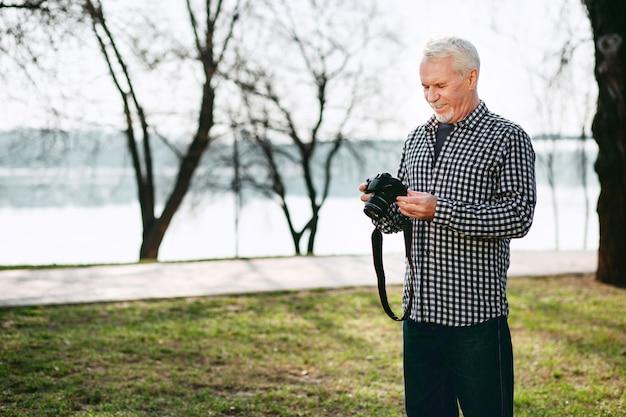 Stwórz obraz. wesoły starszy mężczyzna wpatrując się w dół i używając aparatu