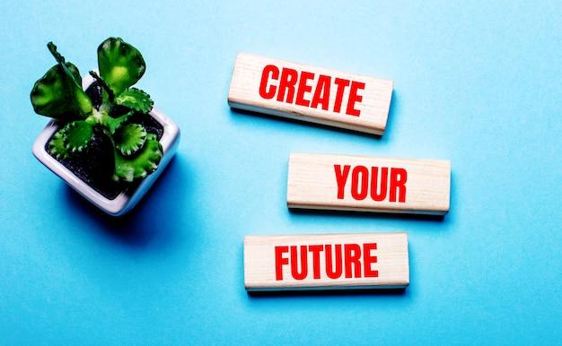 Stwórz swoją przyszłość jest napisane na drewnianych klockach na jasnoniebieskiej powierzchni w pobliżu kwiatu w doniczce