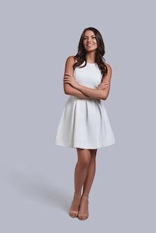 Stworzony, by być modelką. pełna długość atrakcyjnej młodej kobiety w białej sukni patrzącej na kamerę i uśmiechającej się stojąc na szarym tle