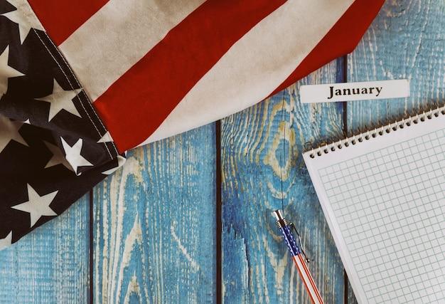 Stycznia miesiąca roku kalendarzowego flaga stanów zjednoczonych ameryki symbol wolności i demokracji z pustego notatnika i pióra na biurowym drewnianym stole