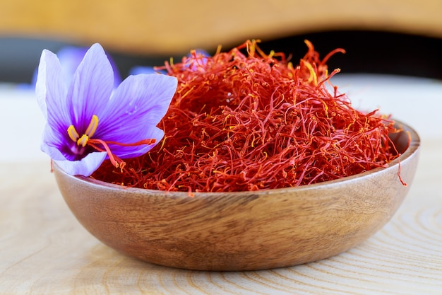 Stygmaty szafranu i krokusa kwitną w drewnianym talerzu. gotowanie przypraw szafranowych